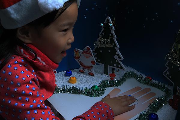小女孩手按壓超低電壓晶片點亮耶誕樹上的LED燈